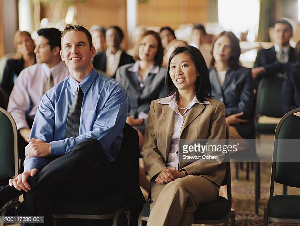 Business professionals sitting in audience at conference