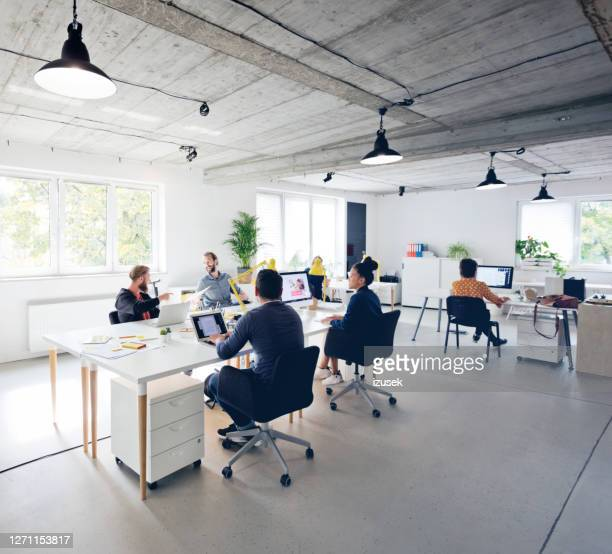 business professionals working at new office desk - working stock pictures, royalty-free photos & images
