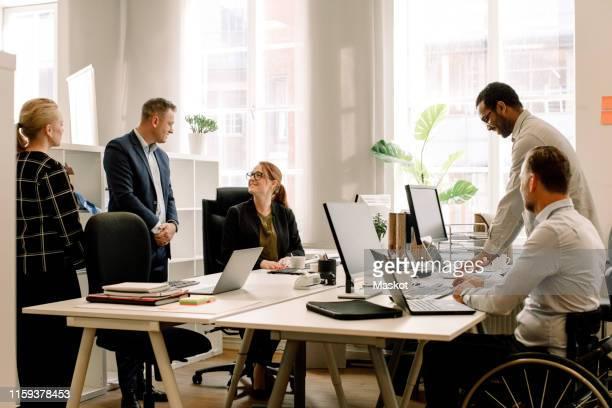 business professionals working together at desk in office - ethnische zugehörigkeit stock-fotos und bilder