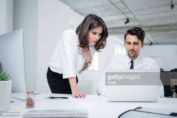 business professionals working together on laptop in office - izusek stock pictures, royalty-free photos & images