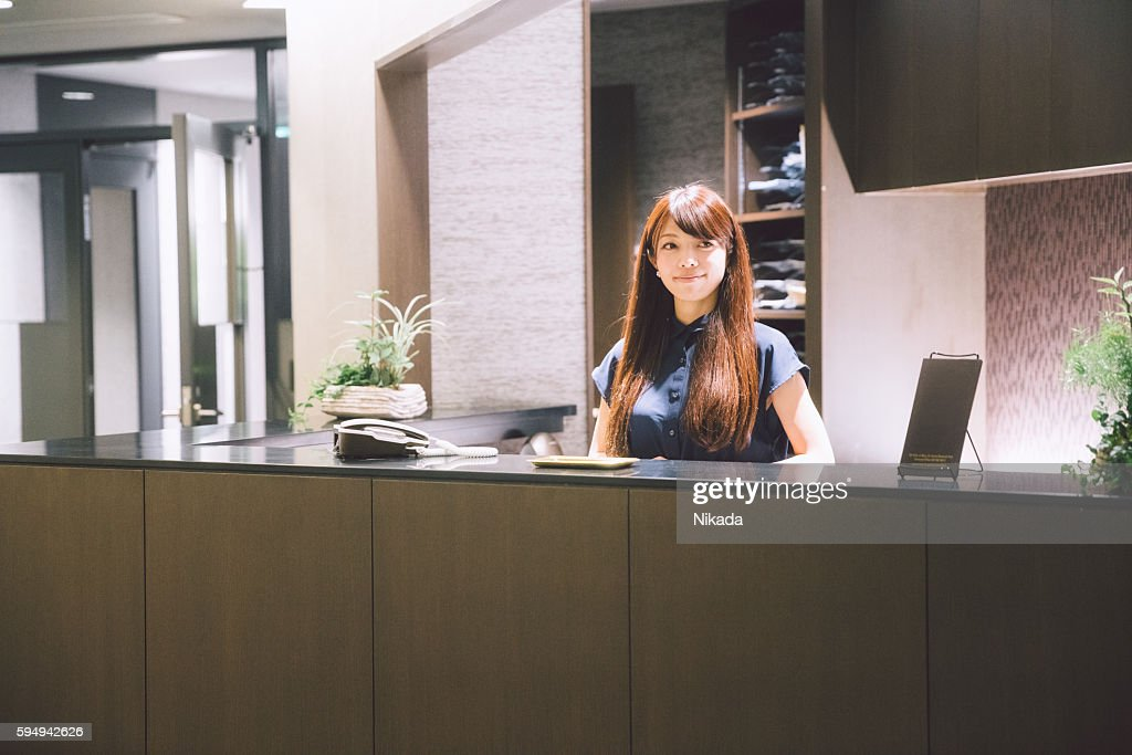 Business reception - woman standing greeting guests in lobby : Stock Photo