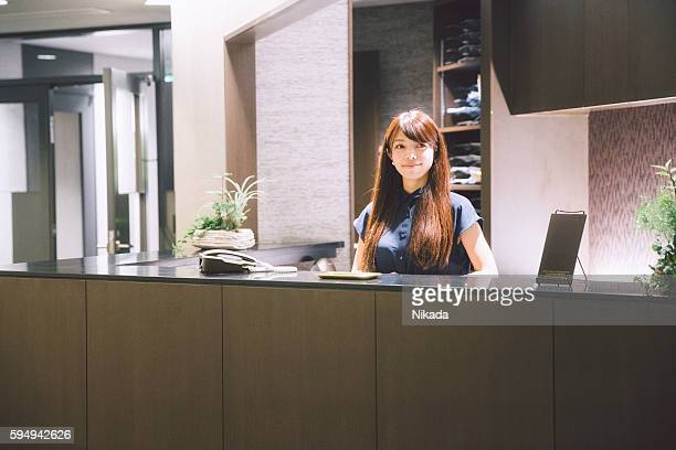business reception - woman standing greeting guests in lobby - 受付 ストックフォトと画像
