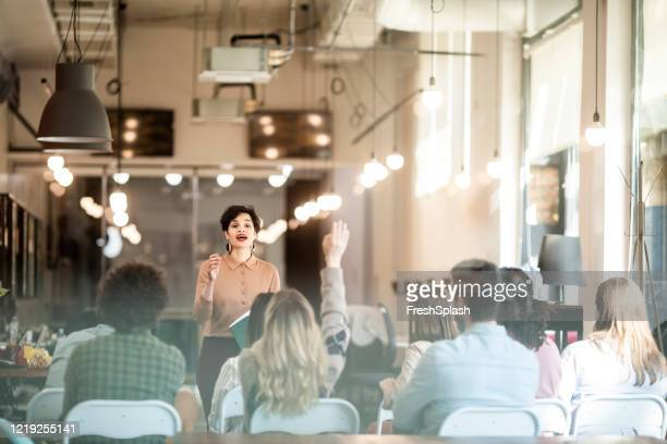 business seminar: businesswoman gives a presentation to a crowd of people - presenter stock pictures, royalty-free photos & images