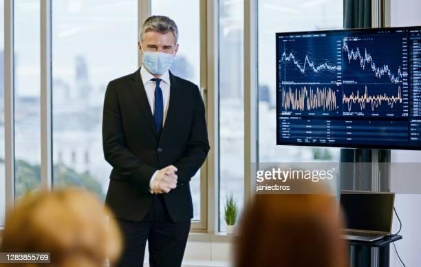 business-seminar. referent in gesichtsmaske analysiert postpandemie-börse - öffentlicher auftritt stock-fotos und bilder