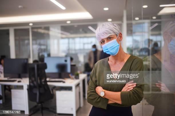 bedrijfs hogere ceovrouw met covidmasker in glasbureau - beschermend masker werkkleding stockfoto's en -beelden