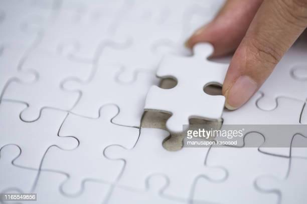 business solutions and success concept. businessman hand connecting jigsaw puzzle. - sierra de vaivén fotografías e imágenes de stock