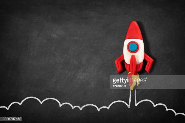 ブラックボード上の宇宙船を持つビジネススタートアップコンセプト - 飛び立つ ストックフォトと画像