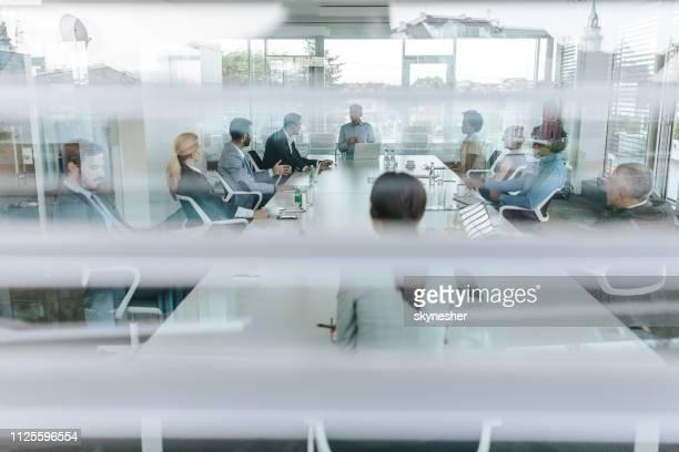 geschäfte zu reden auf einer sitzung am konferenztisch! - geschäftsbesprechung stock-fotos und bilder