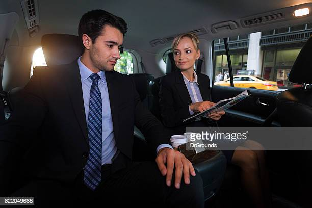 Business team analyzes report in exectuive car