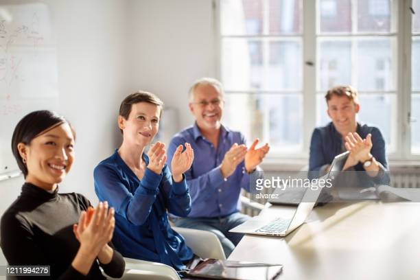 business team applauding after a presentation - applauding stock pictures, royalty-free photos & images