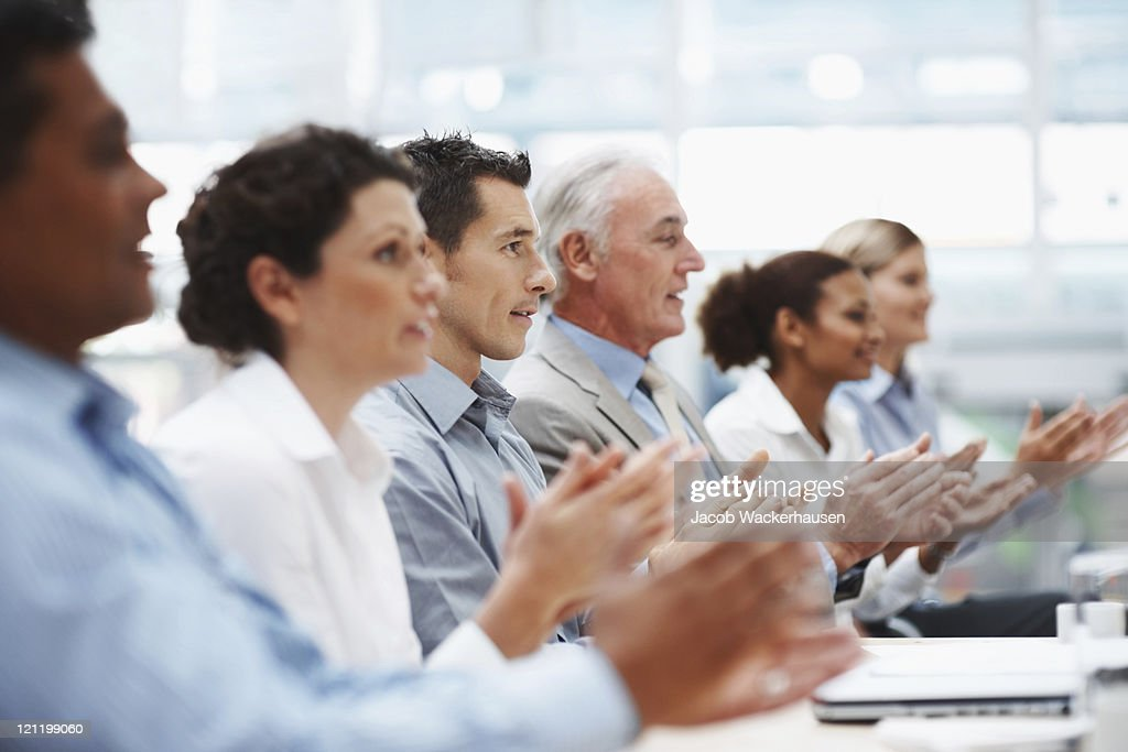 Business team applauding at conference table : Stock Photo