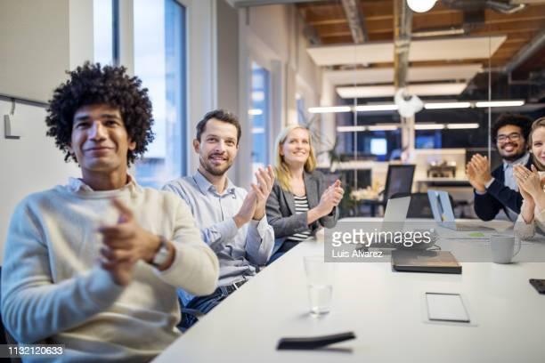 business team applauding while in a meeting at modern office - applaudieren stock-fotos und bilder
