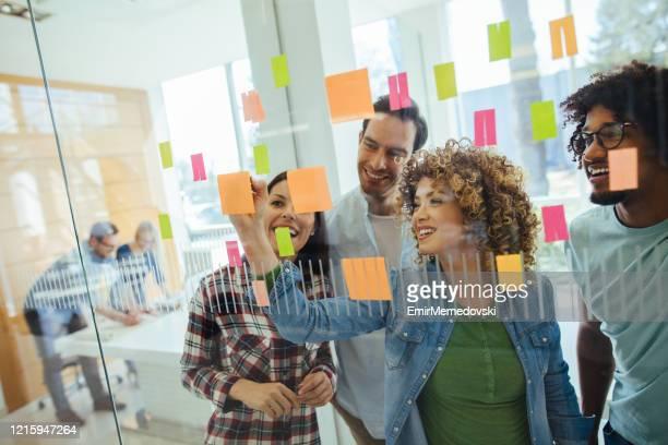 equipe de negócios de brainstorming em frente à parede de vidro - planejamento - fotografias e filmes do acervo