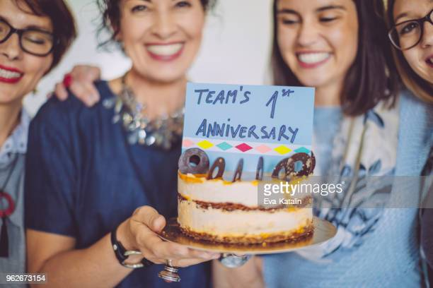 business team celebrating the team's first anniversary - anniversary stock pictures, royalty-free photos & images