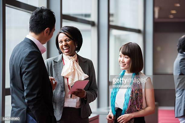 business team consulting in the foyer at a conference - business conference stock pictures, royalty-free photos & images