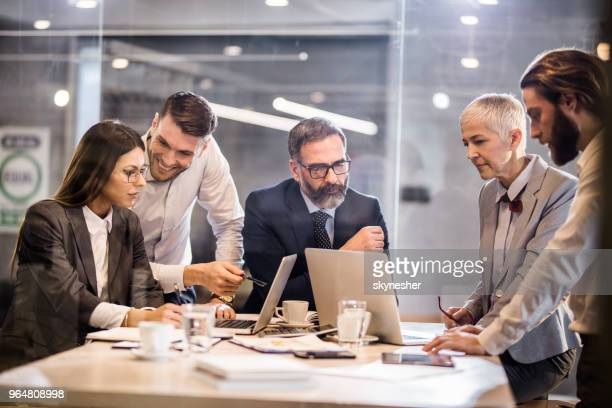 business team cooperating while working on laptops in the office. - staff meeting stock pictures, royalty-free photos & images