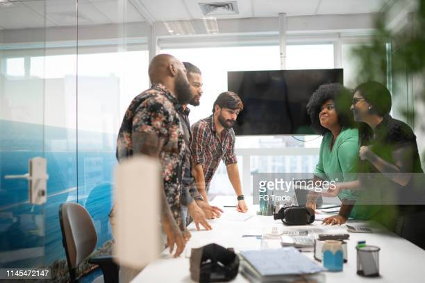 business team discussing plans during business meeting - business plan stock pictures, royalty-free photos & images
