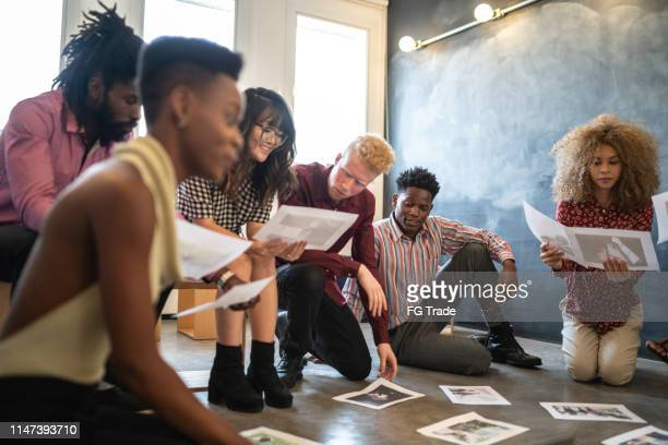 business team discussing some papers on the floor in the office - agility stock pictures, royalty-free photos & images