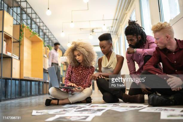 business team discussing some papers on the floor in the office - creative occupation stock pictures, royalty-free photos & images