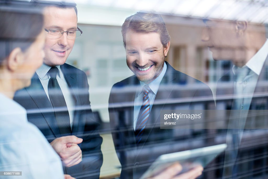 Business team discussing work on a tablet : Stock-Foto