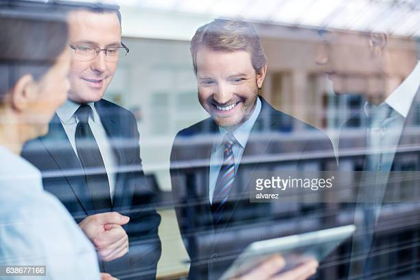 Business team discussing work on a tablet
