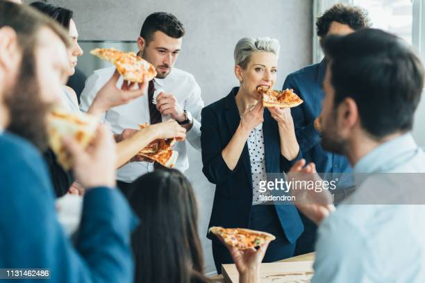 business team eating pizza - work party stock pictures, royalty-free photos & images
