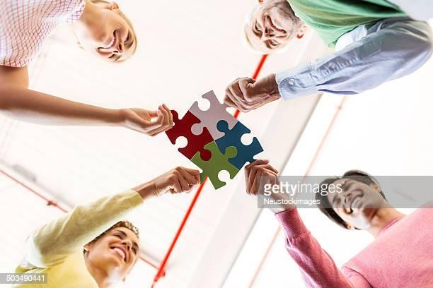 Business Team Fixing Jigsaw Pieces