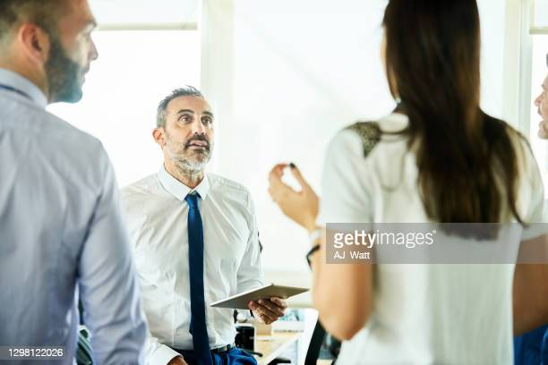 business team having a meeting - mid adult stock pictures, royalty-free photos & images