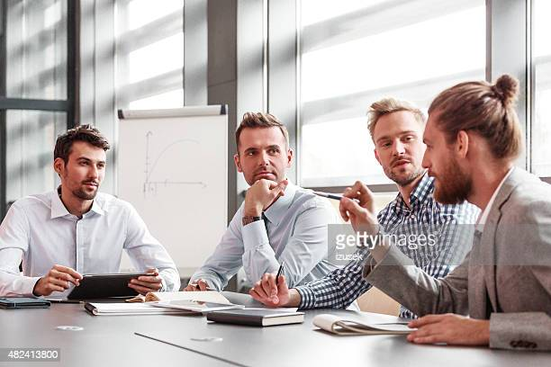 business team having meeting in a board room - izusek stock photos and pictures