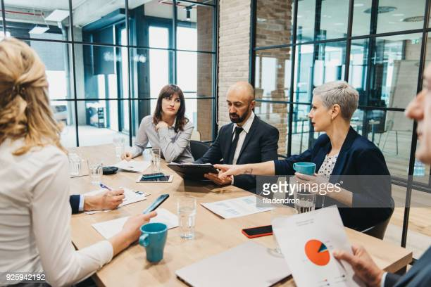 business team having meeting in an office - analysing stock pictures, royalty-free photos & images