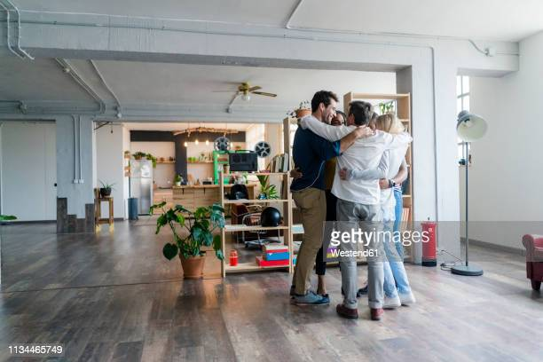 business team huddling in loft office - huddle stockfoto's en -beelden
