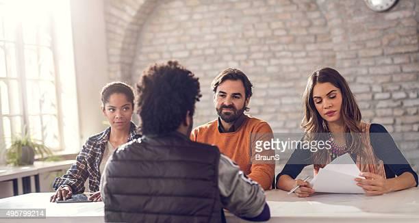 Negocios equipo escucha su potencial colega en la entrevista de trabajo.