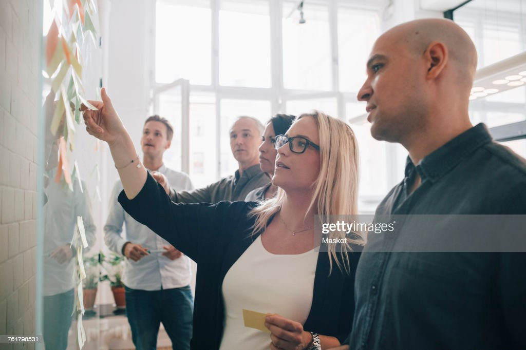 Business team looking at adhesive notes in board room during meeting : Stock-Foto
