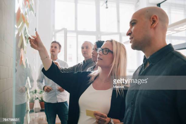 business team looking at adhesive notes in board room during meeting - werkplaats stockfoto's en -beelden