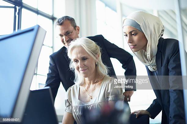 Business team looking at personal computer at office desk
