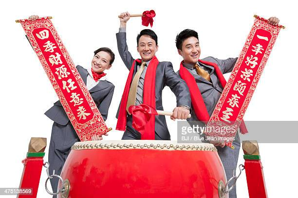 Business team playing traditional Chinese red drum and showing couplets