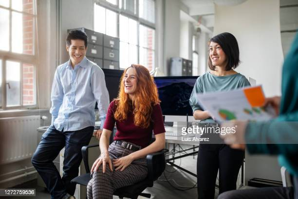 business team smiling during a discussion in office - employee engagement stock pictures, royalty-free photos & images