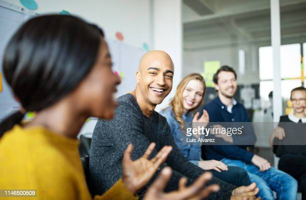 business team smiling during a meeting - employee engagement stock pictures, royalty-free photos & images