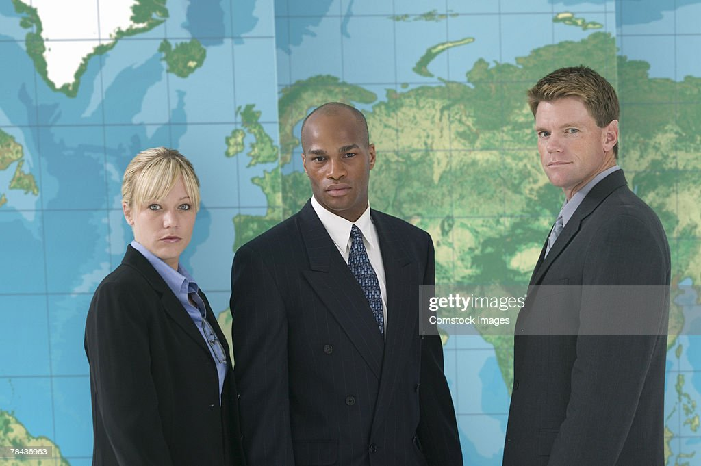 Business team standing in front of world map : Stockfoto