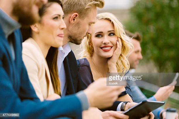 business team talking outdoor, using smart phones - izusek stock photos and pictures