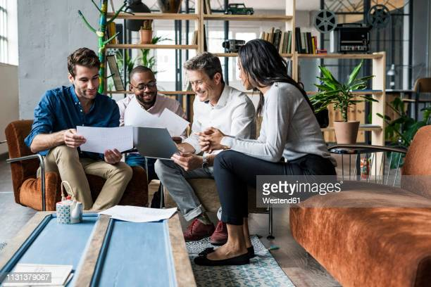 business team using laptop and discussing documents in loft office - four people stock pictures, royalty-free photos & images