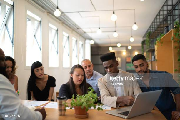 business team (including special needs woman) using laptop on modern office - differing abilities female business stock pictures, royalty-free photos & images