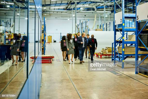 business team visiting  in factory - delegating stock photos and pictures