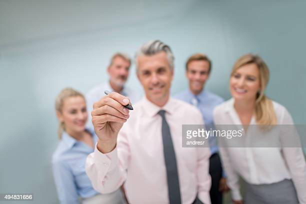 Business team writing with a pen