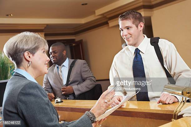 Business traveler checking hotel bill with the front desk associate
