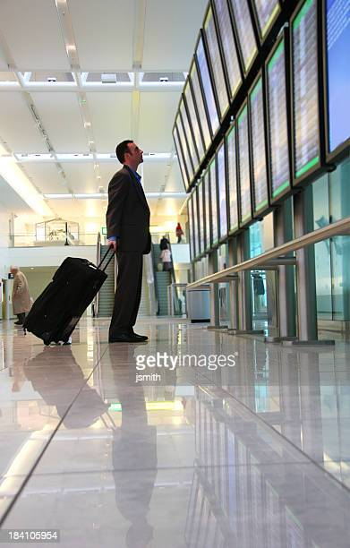 Business Traveler with luggage looks at departure schedule