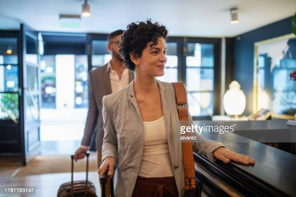 business travelers arriving at hotel reception desk - corridor stock pictures, royalty-free photos & images
