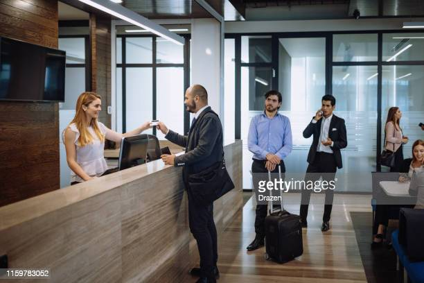 business travelers checking in luxury hotel - hotel stock pictures, royalty-free photos & images