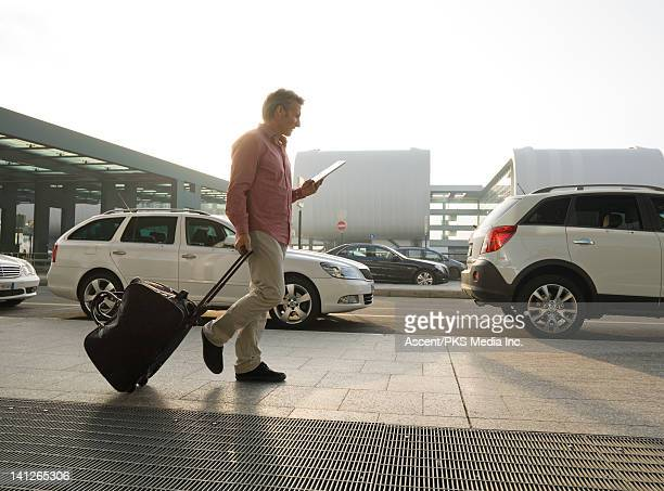 Business traveller checks digital tablet, airport