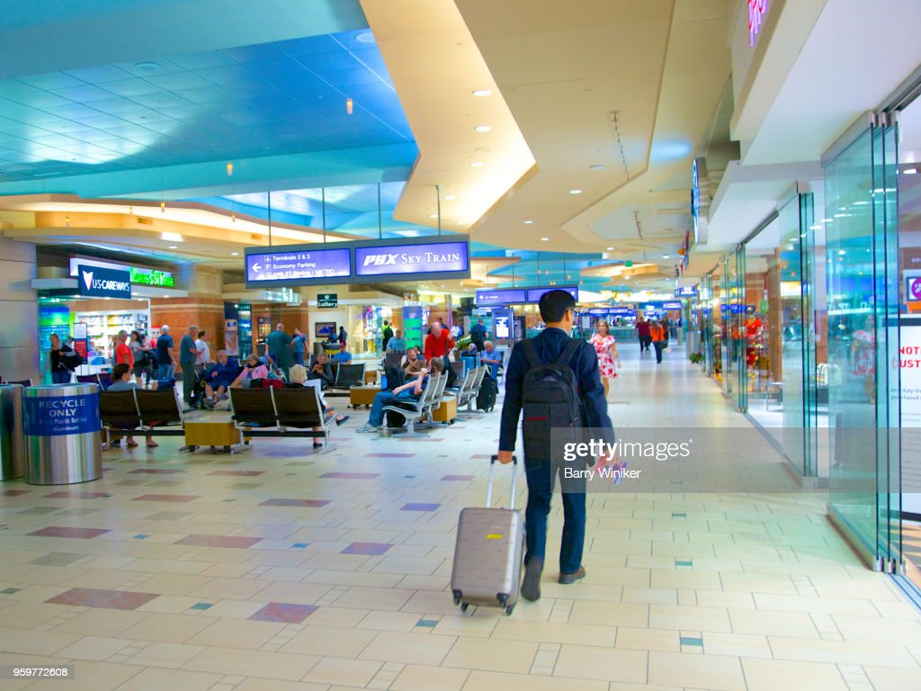 Business traveller with roller bag moving through airport terminal, Phoenix, AZ : Foto stock